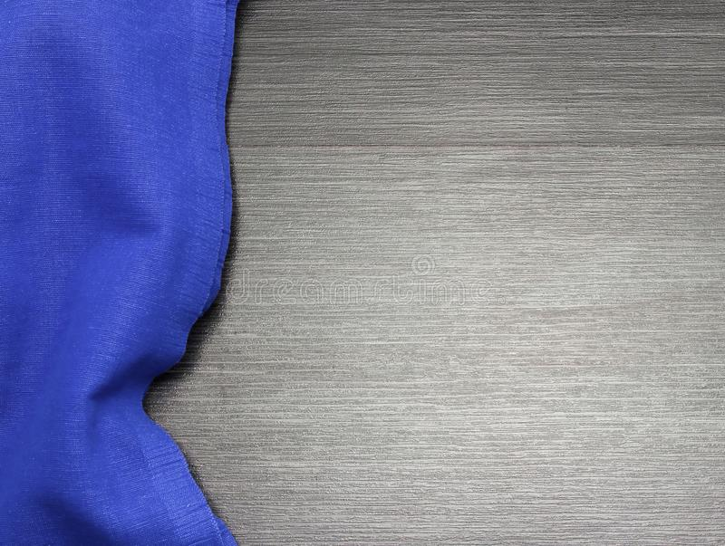 Blue tablecloth on wooden table for background. Fabric texture. Wooden texture. Top view. Copy space. Template des. Blue tablecloth on wooden table for stock photography