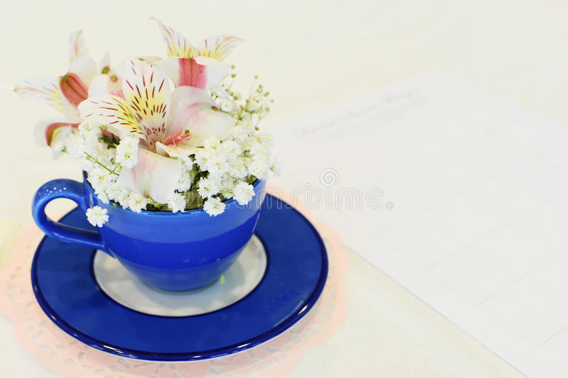 Blue Tea Cup with Flowers. A tea cup centerpiece filled with flowers. The cup is filled with baby`s breath and pink lily like flowers stock photo