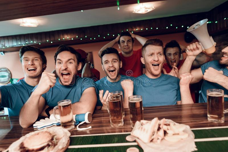 Blue team fans cheering at bar in sports bar with sad red team fans in background. They are watching football game stock photos