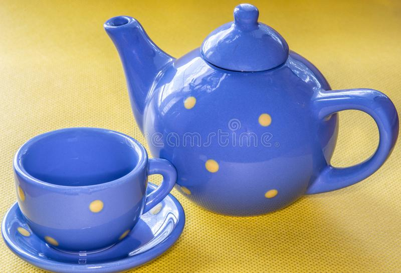 Blue teapot and cup on a saucer for tea on a yellow background. stock photo