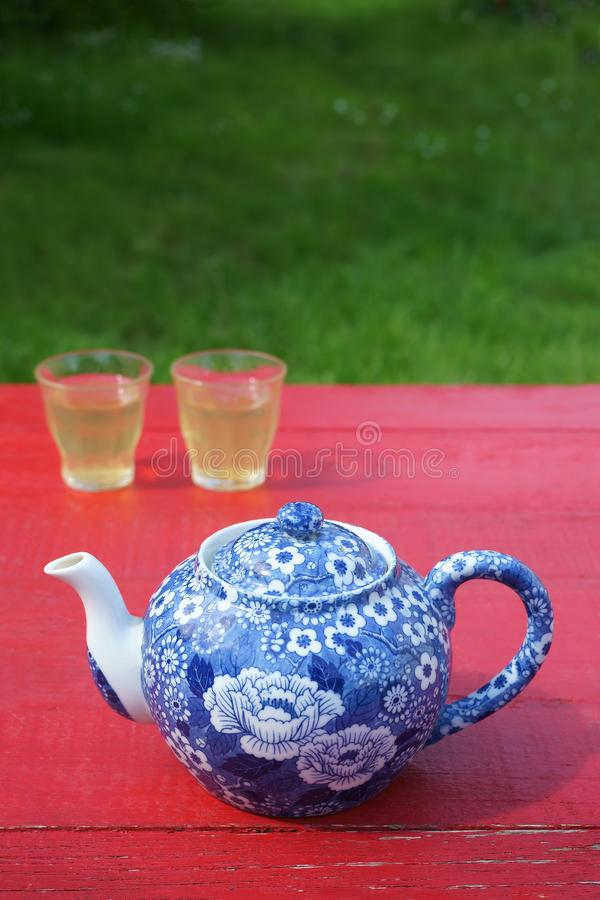 Blue teapot Two glasses filled with tea Red table Outdoor. A blue and white floral decorated porcelain teapot and a two glasses filled with tea placed on a red royalty free stock image