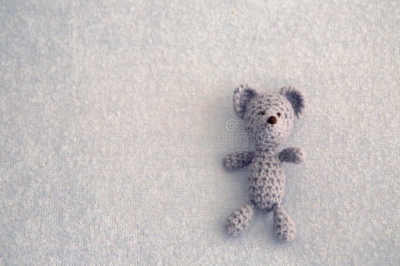 Blue teddy bear knitted toy. Lies on a blanket royalty free stock images