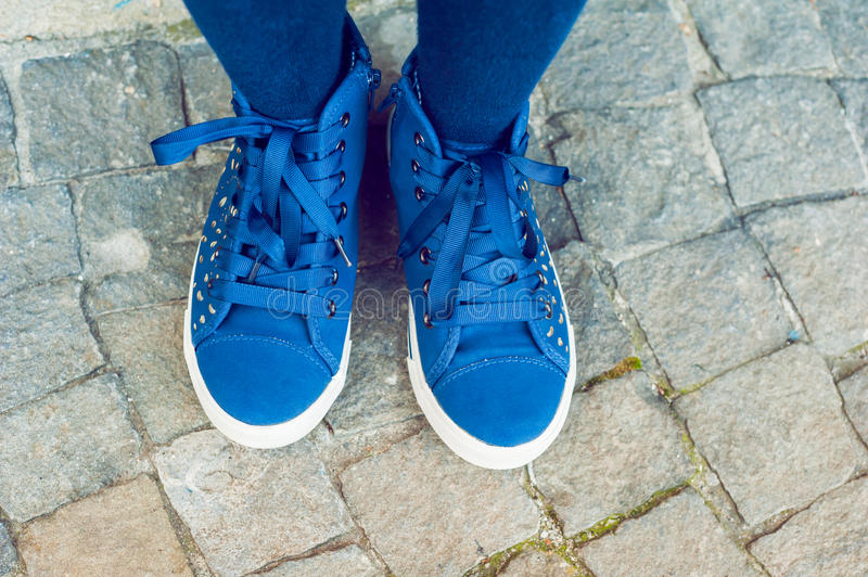 Blue tennis shoes on a stone background stock photo