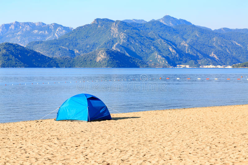 Blue tent on the beach with mountains. In sunny day royalty free stock photo