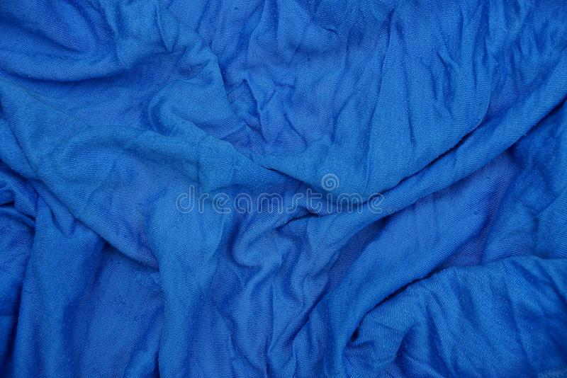 Blue texture of a piece of crumpled cloth from clothes. Blue background of a fragment of crumpled cloth from clothes stock photo