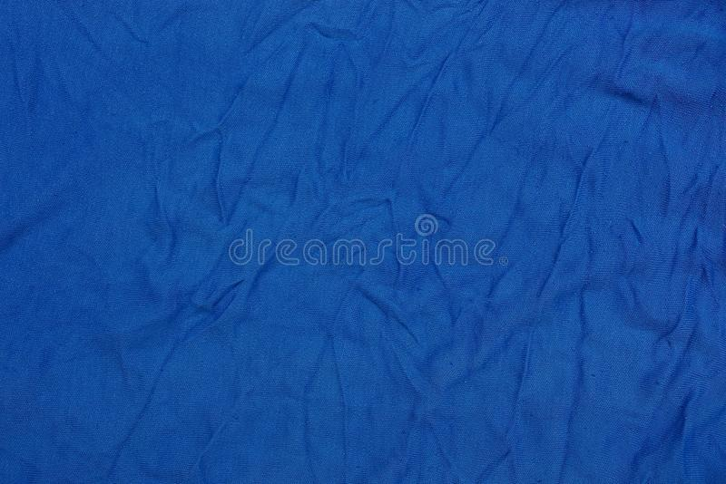 Blue texture of a piece of crumpled cloth from clothes. Blue background of a fragment of crumpled cloth from clothes royalty free stock image