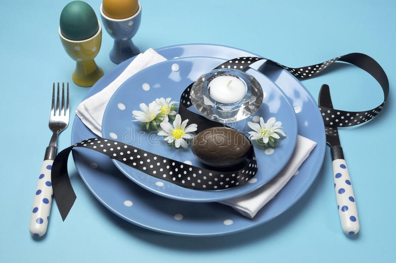 Blue theme Happy Easter dinner table setting with blue polka dot plates. Happy Easter dinner table setting with blue polka dot plates, and decorations against a royalty free stock photo