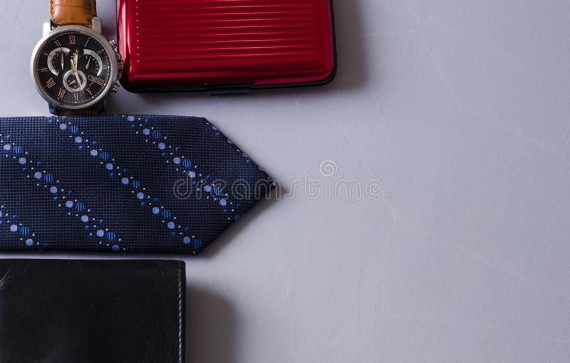 Fashion Accessories for a Business Man. A blue tie with a leather wallet ,credit card holder,a stylish watch and spectacles for a business man royalty free stock photography