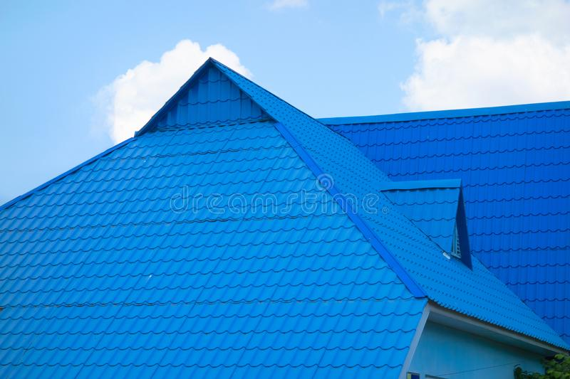Blue tiled roof of house on sky background in day time. Object of modern townhouse or other real estate construction royalty free stock photography