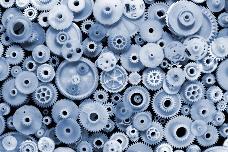 Blue tinted plastic gears and cogwheels on black background royalty free stock image