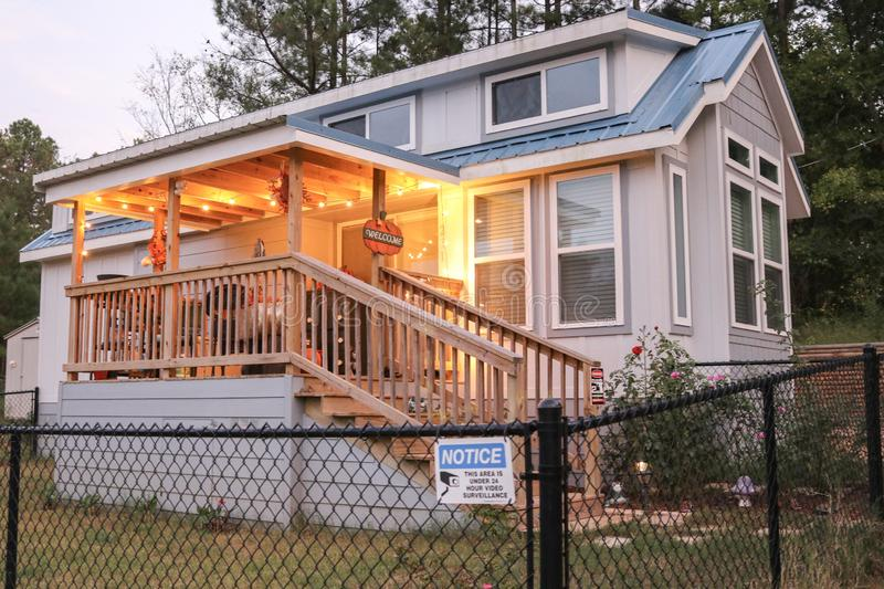 Blue tiny house in the country with warm porch lighting and a black chain fence around the yard stock photography
