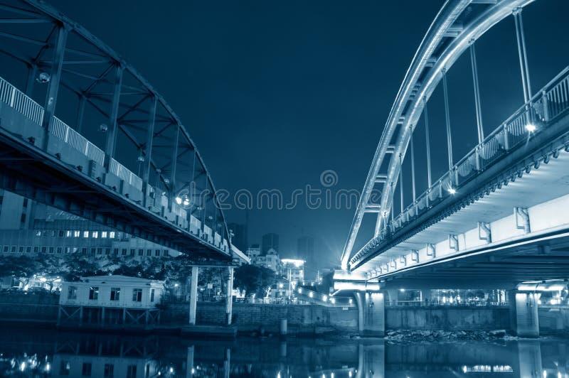 Jiangmen, Guangdong, China, the Jiangmen Iron bridgeLeft and Shenglli bridgeRight at night. Blue tone, toned imaged,Jiangmen Iron bridge built in 1983 and stock photography