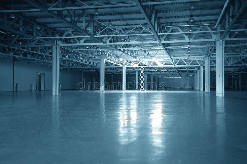 Blue toned empty storehouse royalty free stock photography