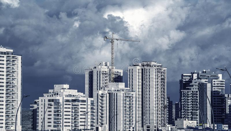 Blue toned image of High rise tower crane and new residential buildings. stock photo