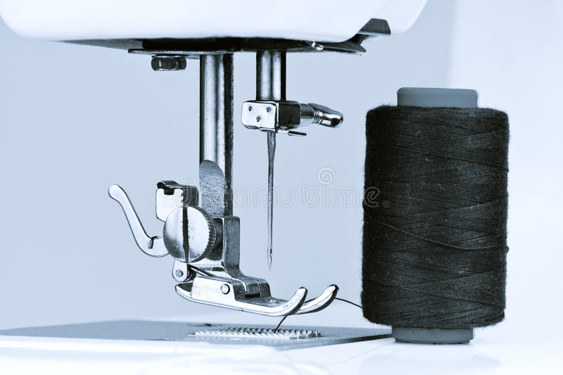 Blue toned sewing machine and reel with thread stock photography