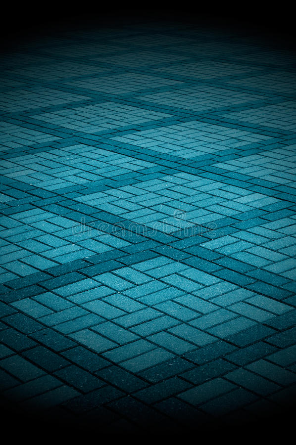 Blue-Toned Tiled Pavement. A spotlit blue-toned tiled pavement as a background stock photo