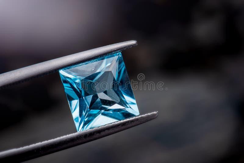 Blue topaz gemstone jewelry photo with dark lighting background. Blue topaz gemstone jewelry photo with black and dark lighting background stock image