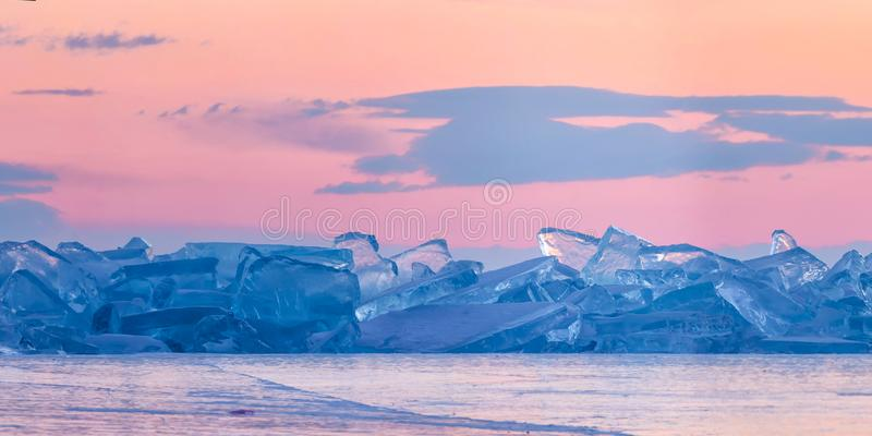 Blue toros of Baikal against the background of the pink sky of the dawn and purple clouds. Wide panorama.  stock illustration