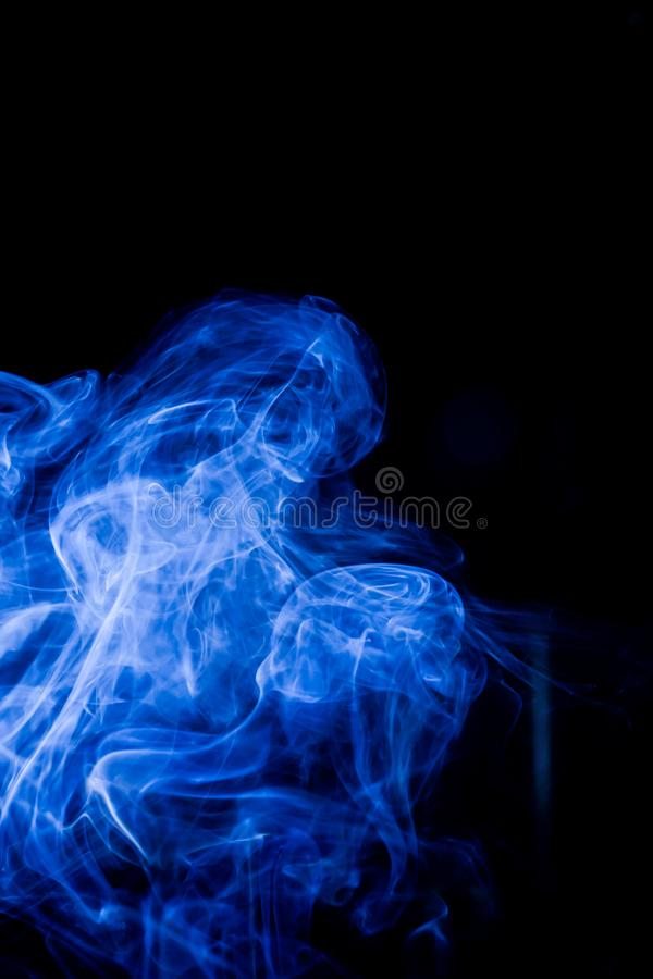 Blue toxic fumes movement on a black background. Abstract, art, beautiful, color, curve, design, flowing, fumigate, light, motion, mystery, nobody, pattern royalty free stock photo