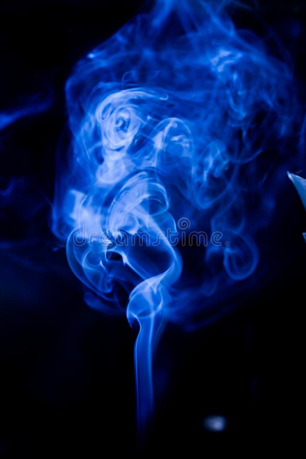 Blue toxic fumes movement on a black background. Abstract, art, beautiful, color, curve, design, flowing, fumigate, light, motion, mystery, nobody, pattern royalty free stock photography