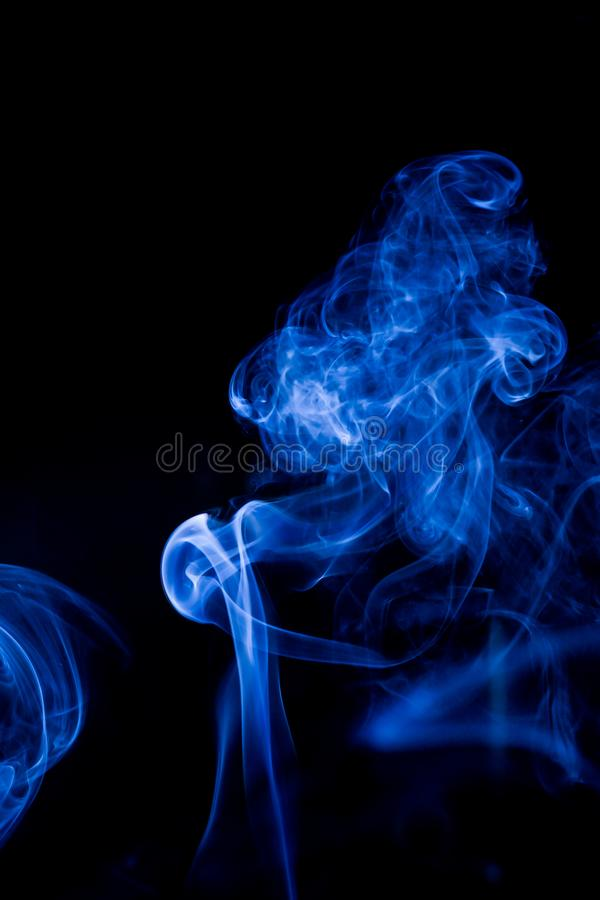 Blue toxic fumes movement on a black background stock image