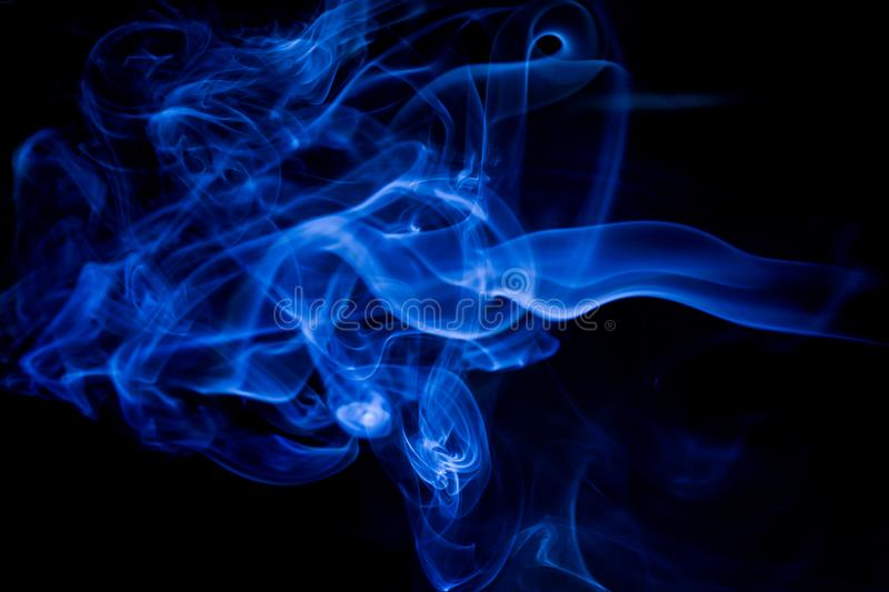 Blue toxic fumes movement on a black background stock photos