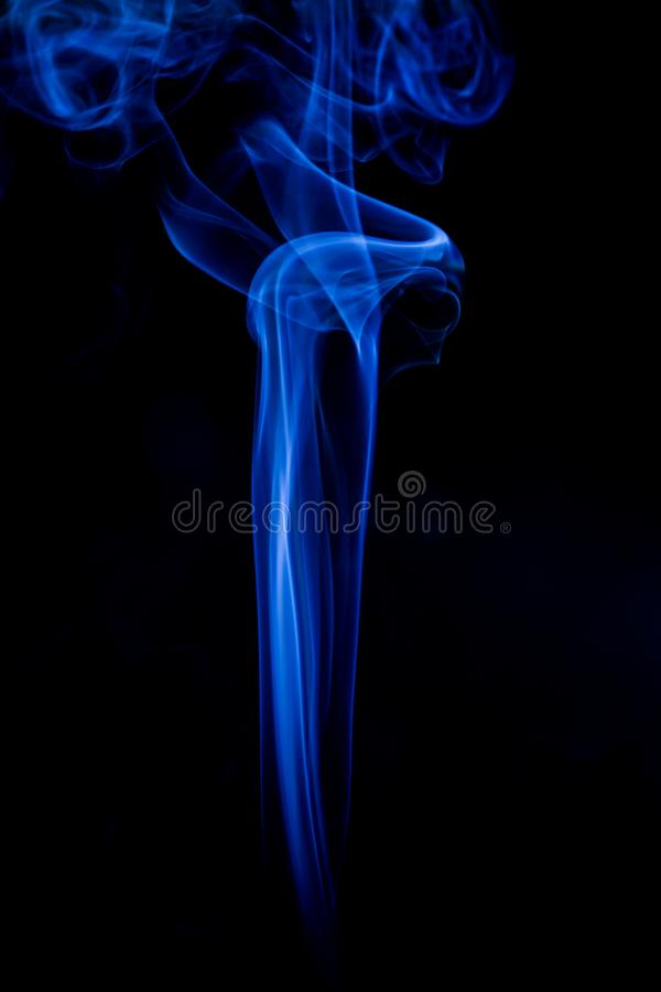 Blue toxic fumes movement on a black background. Abstract, art, beautiful, color, curve, design, flowing, fumigate, light, motion, mystery, nobody, pattern royalty free stock image