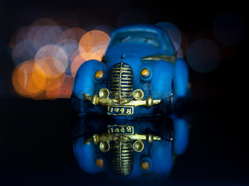 Blue toy car on a black background.Beautiful bokeh. Beautiful blue model of toy on a black background royalty free stock images