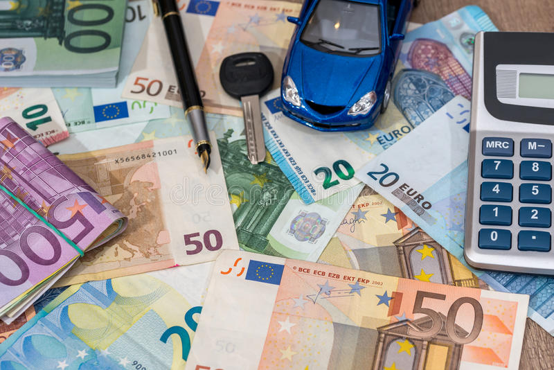 Blue toy car with euro banknotes, calculator. And pen royalty free stock photo