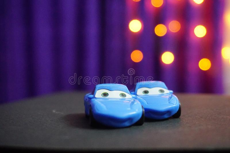 2 blue toy cars of a cars movie. 2 blue toy cars looking cute with a purple and yellow light surface stock photos