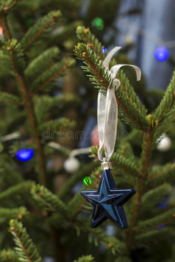 Blue toy - a star with a ribbon on a Christmas tree with a garland, on a blurred background. Beautiful blue toy - a star with a ribbon on a Christmas tree with a stock photos