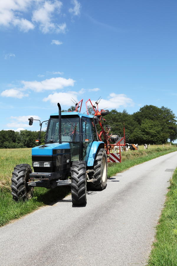 Blue Tractor And Hay Rake Summer Road. A vertical photo of a blue tractor with a hay rake attached parked alongside an empty farm road with dairy and beef cattle stock images