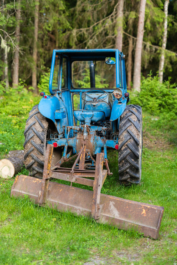 A blue tractor standing in a forest. A blue tractor standing in a green forest royalty free stock photos