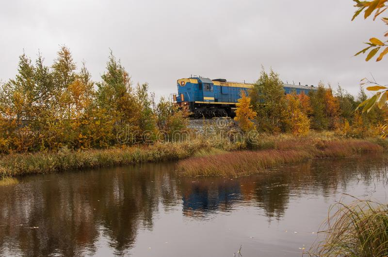 Blue train are going through yellow forest near the river. Autumn trees are reflecting in the water.  stock image