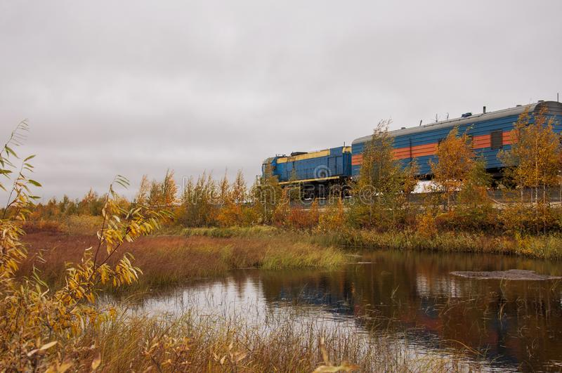 Blue train are going through yellow forest near the river. Autumn trees are reflecting in the water.  royalty free stock image