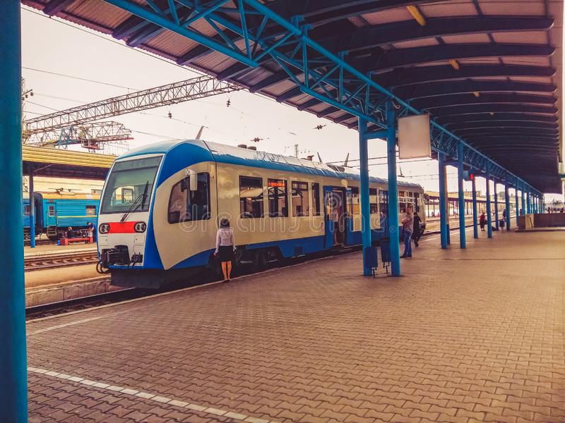 Blue train stands before departure. A woman conductor and several passengers are standing on the platform stock photo