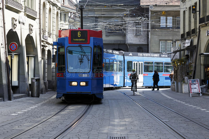 The blue tram in Bern. Bern, Switzerland - April 20, 2017: The blue tram turns from one street to the other in the old town. Along the tracks a cyclist and other royalty free stock image