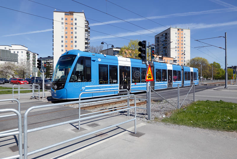 Blue tram in Solna. Solna, Sweden - May 6, 2016: Blue tram on the Tvarbanan line at the road crossing with Gransgatan royalty free stock photos