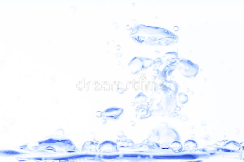 Blue transparent aqua water splash with bubbles on white clean background abstract royalty free stock photography