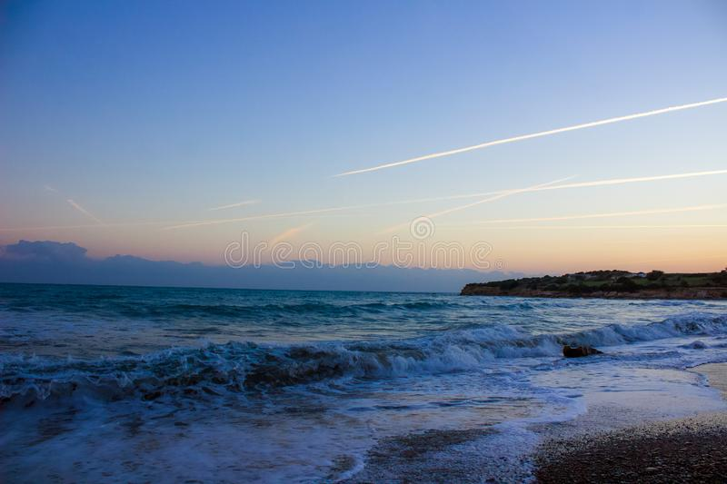 Blue travel hour, Mediterranean sea, air trails and setting sun. Early evening at the beach, sunsetting across the horizon to a beautiful background of air royalty free stock photography