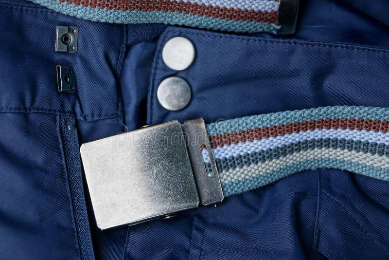 Blue trousers with buttons and zip with a striped belt with an iron buckle stock image
