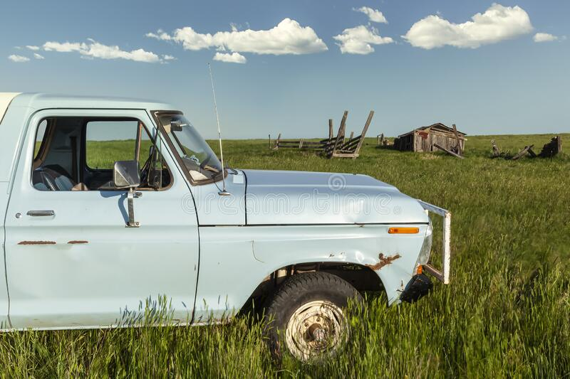 Blue truck in an open field with old rundown barn shed and blue sky cloud background. Old blue pickup truck close up in an open field with old rundown barn shed royalty free stock photo