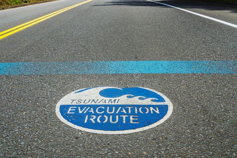 Tsunami evacuation route road sign on the asphalt, Highway 101, Oregon, USA. Blue Tsunami evacuation route road sign on the asphalt, Highway 101, Oregon, USA royalty free stock images