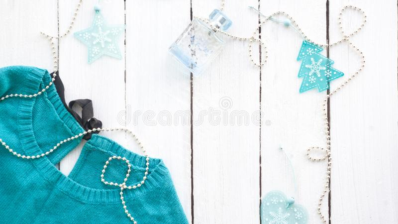 Blue, turquoise sweater on a white wooden background with new-year decorations. Blue, turquoise sweater on a white wooden background with New Year decorations stock image