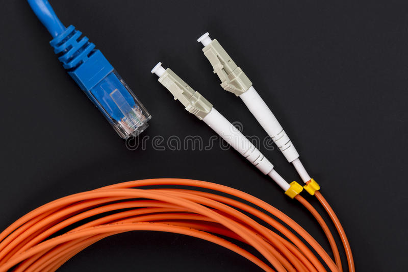 Blue twisted pair patch cord with fiber optics orange cable on dark background stock photos