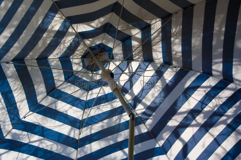 Blue umbrella. With white strips royalty free stock photo