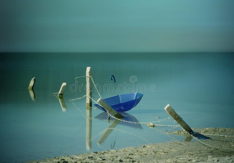 Blue umbrella behind the fence. royalty free stock photography