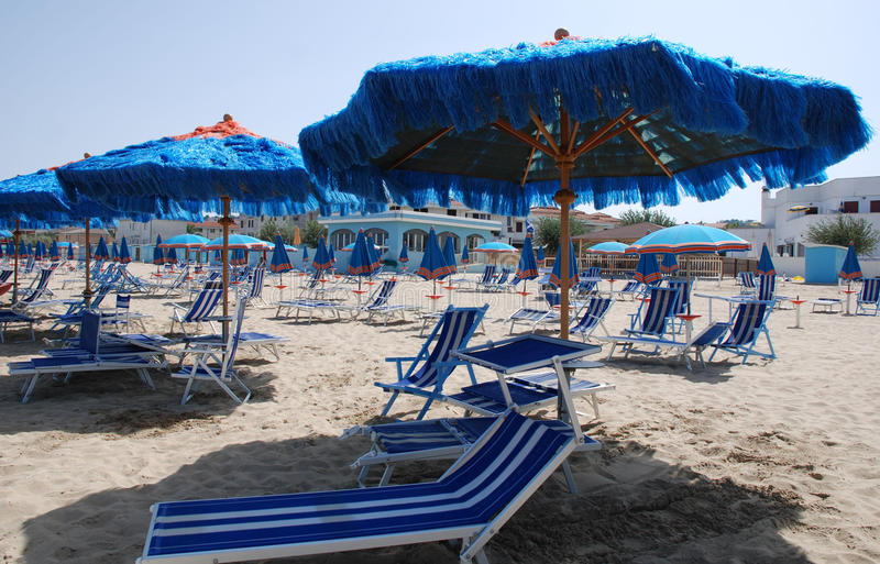 Blue Umbrellas and Deck Chairs. Blue and white stripy beach umbrellas and deck chairs on a beach on a sunny summers day stock photography