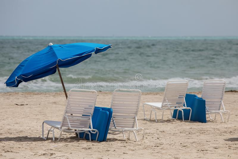 Blue umbrellas and white lounge chairs in the South Beach, Miami royalty free stock image