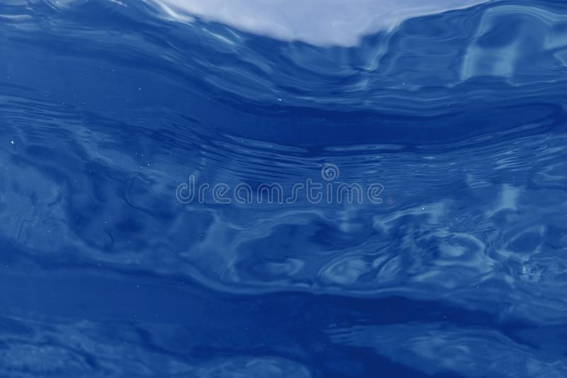 Blue underwater bokeh ,light particles Abstract. Monochrome blue style Background. stock photography
